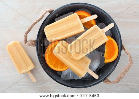 Homemade orange popsicles in a rustic ice filled tin pail