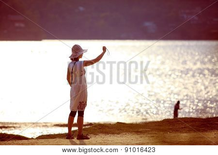 woman making a photo on the beach