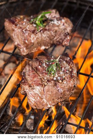 Delicious beef steaks on grill with flames