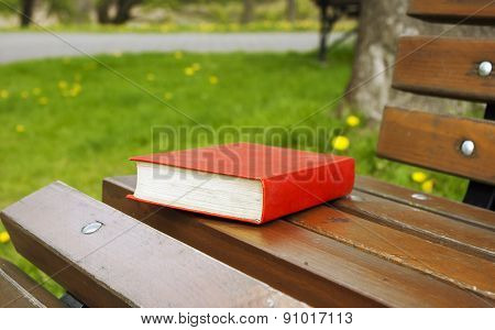 Close Book In The Red Cover Lies On A Park Bench