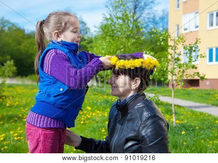 Daughter Puts On Her Mom's Head A Wreath Of Dandelions