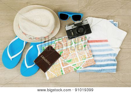 Summer vacation clothes, shoes and hat on wooden background