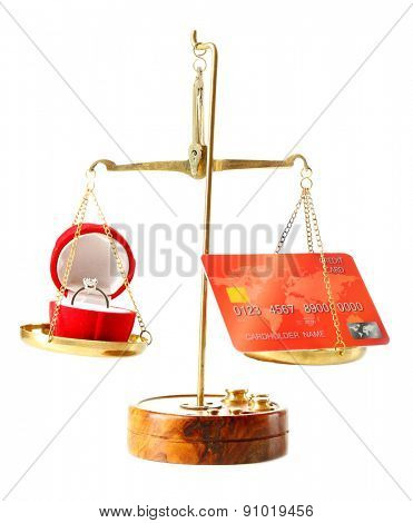 Wedding ring and credit card in balance scales, isolated on white