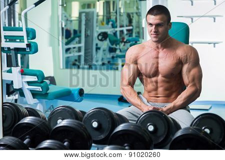 Muscular arm in the gym. Hand holding a dumbbell in suspense.