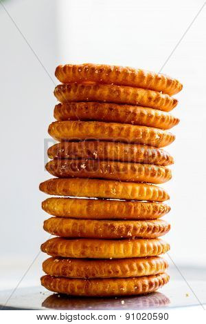 Freshly baked salt biscuits stacked on one another on a plain background
