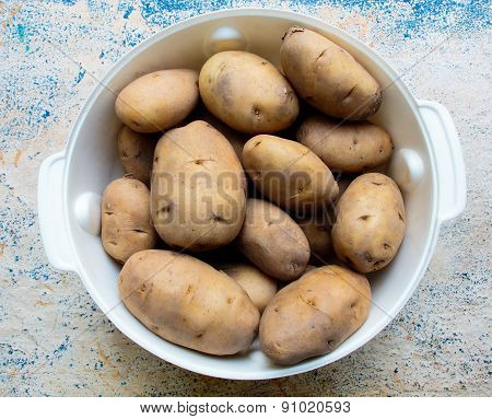Old stock of potatoes kept in a vessel on a blurred background