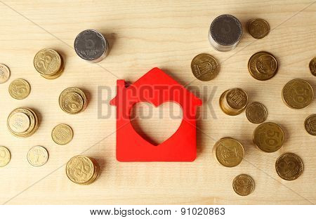 Model of house with coins on wooden background