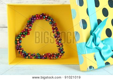 Bright heart in present box on wooden table