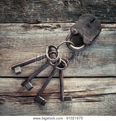 Old Rusty Lock With Keys On Wooden Background.