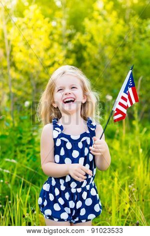 Laughing Blond Little Girl With Long Curly Hair Holding American Flag, Outdoor Portrait On Sunny Day