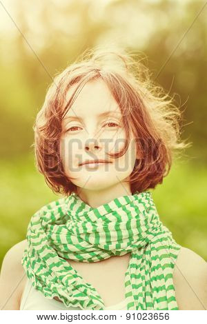 Outdoor Portrait Of Beautiful Young Woman Wearing Green-White Striped Scarf With Wind In Her Hair