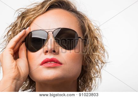 Portrait of blonde in the studio. Blonde in sunglasses on a gray background.