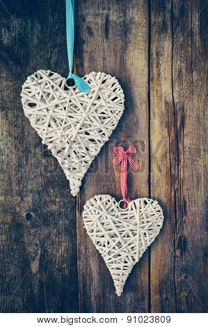 Two Wicker Hearts Hanging On Old Wooden Wall. Retro Stylized.