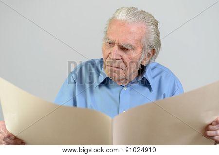 Elderly Man Holding A Blank Big Ocher Paper Sheet
