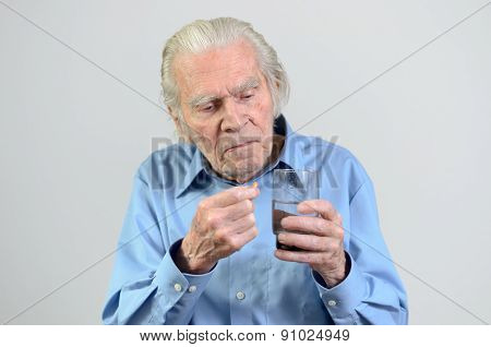 Senior Man Taking The Prescribed Dose Of Medicine