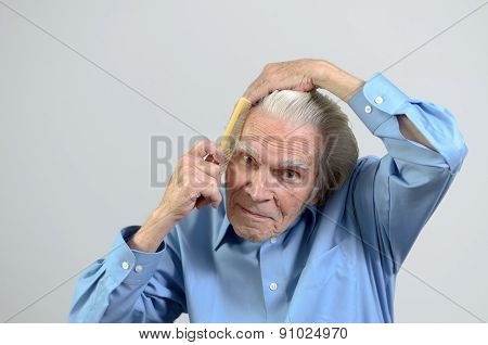 Active Elderly Man Combing His Hair With A Comb