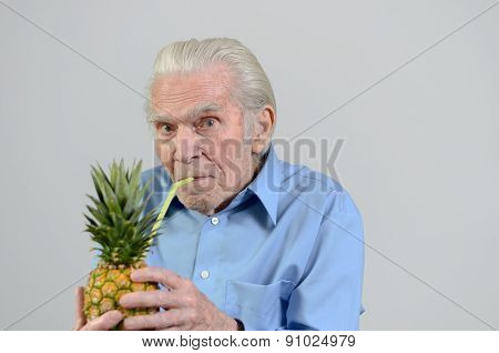 Senior Man Drinking Fresh Pineapple Juice
