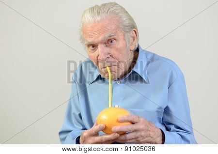 Senior Man Drinking Fresh Grapefruit Juice