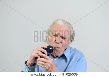 Elderly Man Shaving With A Cordless Electric Razor