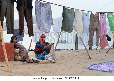 Indian Old Family Sit Near Clothesline On Ghat Near Sacred River Ganges In Varanasi