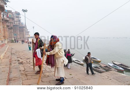 Indian Old Man With His Son Go On Steps Of Ghats In Varanasi