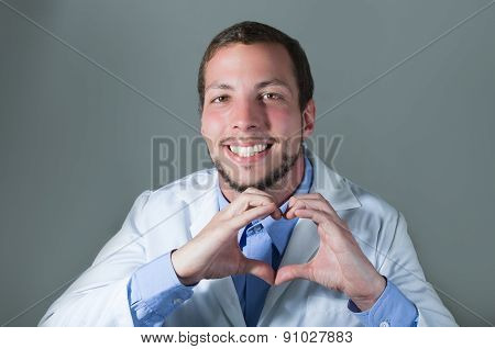 Closeup portrait of handsome young doctor making a heart with hands