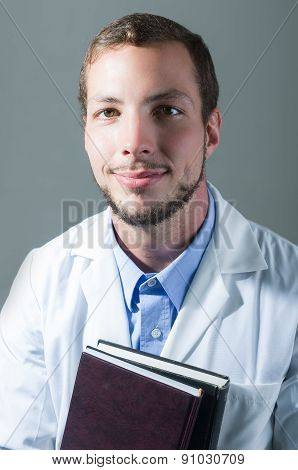Closeup portrait of handsome young doctor holding books