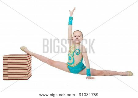 Cute young girl doing gymnastics with cube