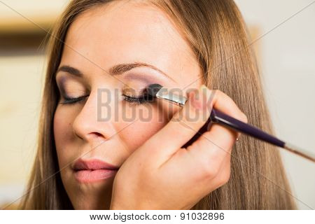 Makeup artist paints the eyebrows model. painting of eyebrows.