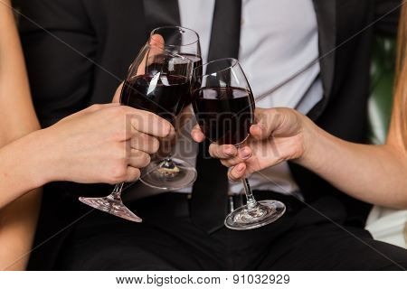 Man and two woman at meeting are drinking wine. Group of happy young people drink wine.