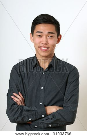 Smiling young Asian man with crossed hands looking at camera.