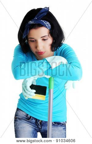 Portrait of tired woman with a mop and sponge.