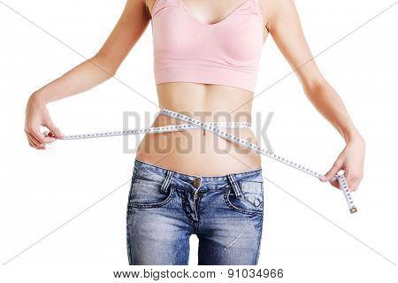 Slim woman measuring her waistline