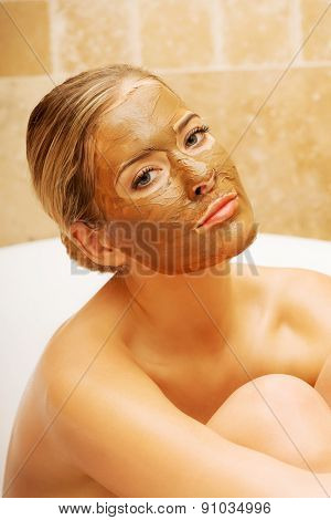 Relaxed woman sitting in a bath with face mask looking at the camera.