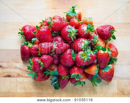 Pile Of Strawberries On Wooden Board