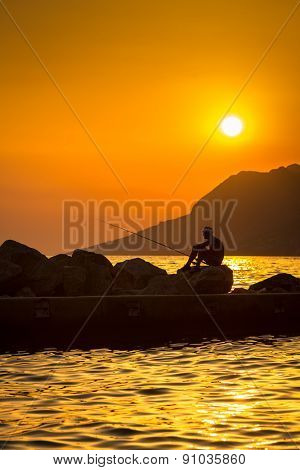 Fisherman silhouette at sunset (color toned image)