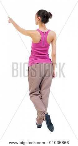 Back view of  pointing woman. beautiful girl. Rear view people collection.  backside view of person.  Isolated over white background. tanned girl shows her legs crossed ahead.