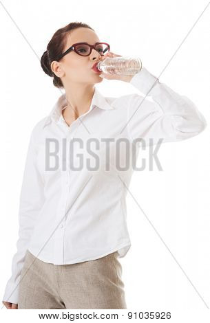 Full length businesswoman drinking water.