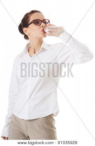 Full length businesswoman drinking water.