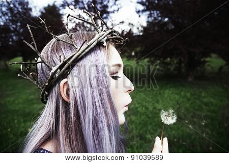 Young woman wearing twig crown and blowing on dandelion