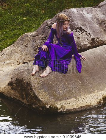 Young woman in purple gown sitting on rocks by a river.