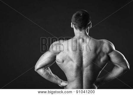 Muscular man bodybuilder. Man posing on a black background, shows his muscles.