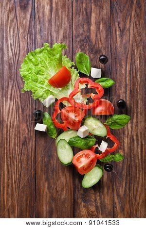 flying salad on wooden background - red tomatoes, pepper, cheese, basil, cucumber and olives