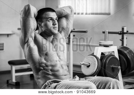 A man pumping abdominal muscles. Man in the gym. Man makes exercises