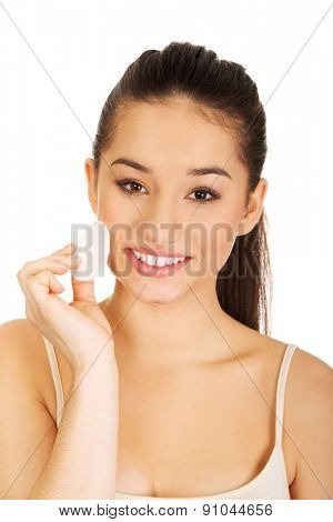 Beautiful woman cleaning make up with cotton pad.