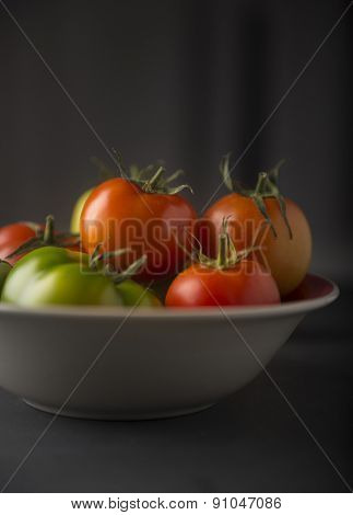Red and green tomatoes in a bowl on black background. Front view.