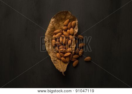 Cleaned almond seeds on a dry almond tree leaf. Artistic composition.