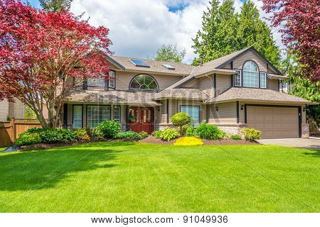 Luxury house with beautiful landscaping on a sunny day. Home exterior.