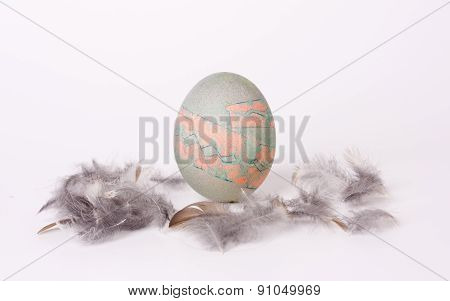 Painted egg with feathers