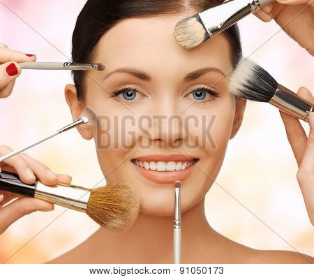 beauty, people and makeup concept - closeup of beautiful woman getting professional make-up with many brushes over beige background